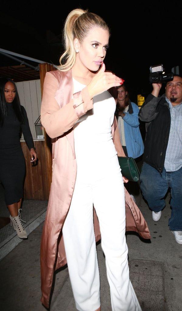 Хлои Кардашян пришла на вечеринку в Голливуде в белом комбинезоне и атласном плаще