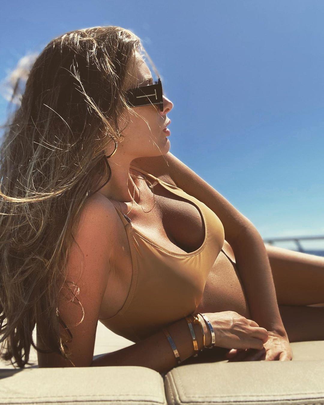 Кэти Топурия в купальнике пытается скрыть животик